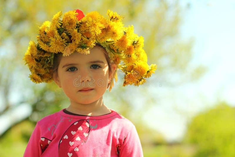 摆在与蒲公英花圈的一个逗人喜爱的两岁女孩的春天画象 库存图片