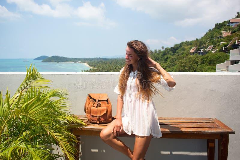 摆在与蓝色海洋的惊人的热带海滩的年轻人相当时髦的肉欲的妇女享受她的假日和一有风summe 免版税库存图片
