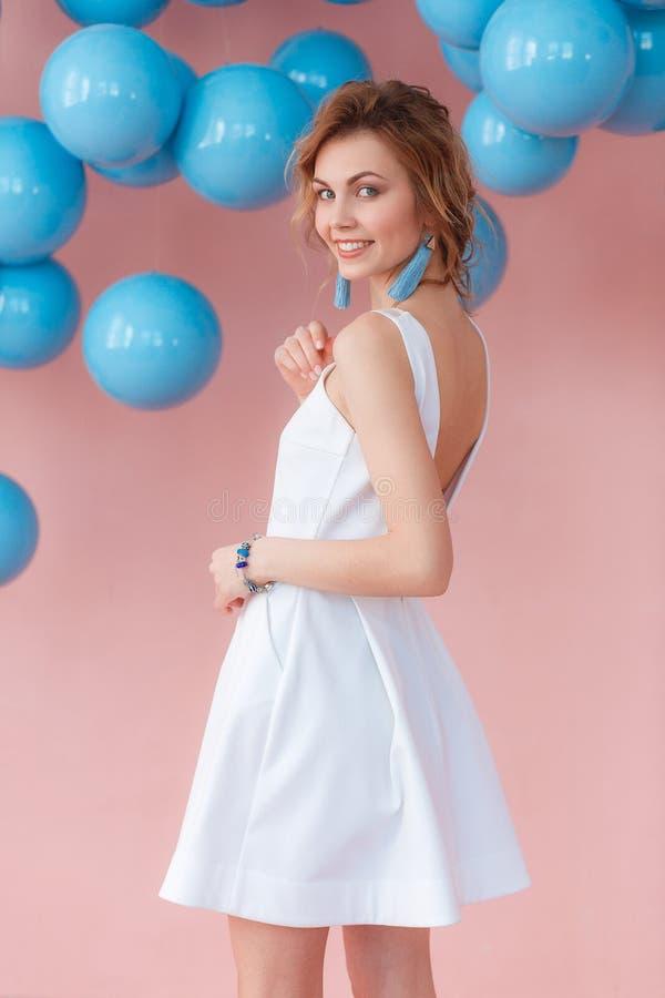 摆在与蓝色球垂悬的桃红色墙壁背景的白色燕尾服的少妇 免版税库存照片