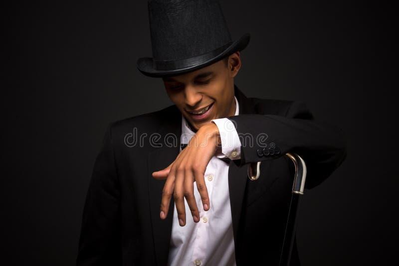 摆在与藤茎的高顶丝质礼帽的英俊的人 免版税图库摄影