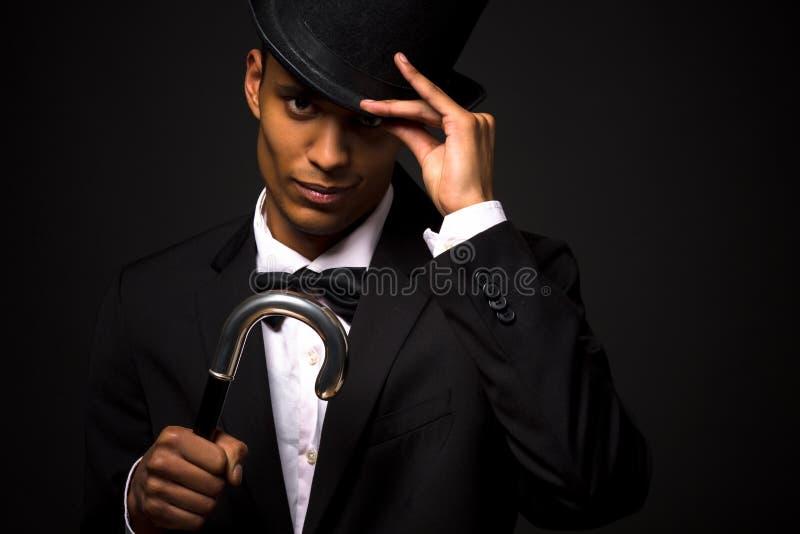 摆在与藤茎的高顶丝质礼帽的英俊的人 库存图片