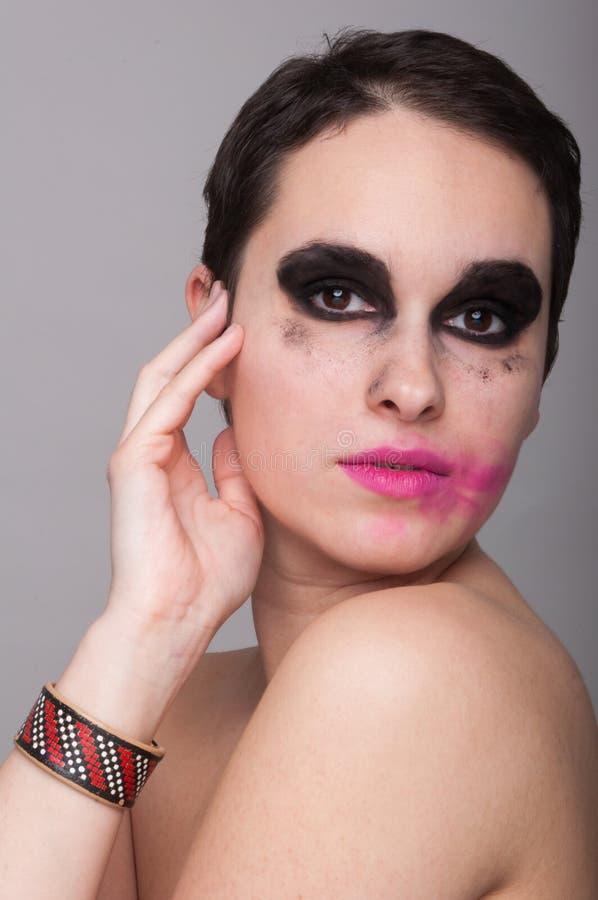 摆在与被抹上的构成的俏丽的妇女 图库摄影