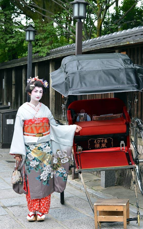 摆在与被拉扯的人力车,京都,日本的Maiko 免版税库存图片