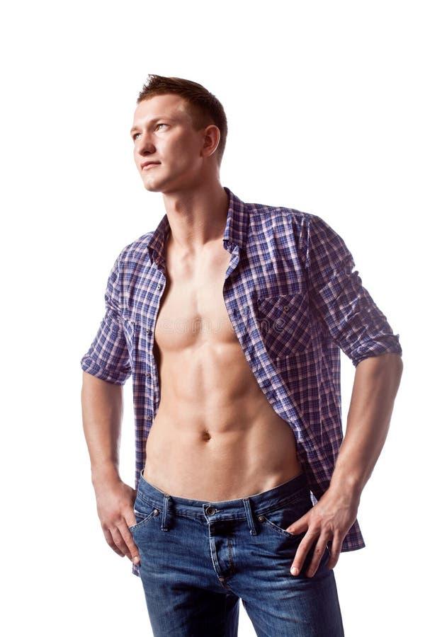 摆在与被解扣的衬衣的性感的英俊的人 免版税图库摄影