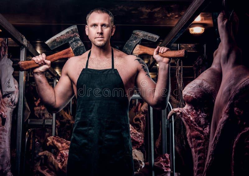 摆在与轴的围裙的赤裸上身的被刺字的屠户在一个被冷藏的仓库里在肉尸体中间 免版税库存照片