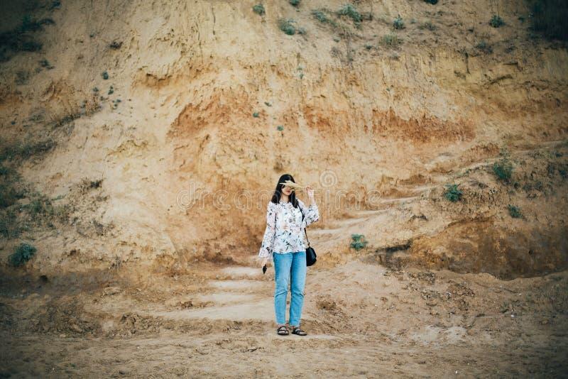 摆在与野花的时髦的行家女孩,拿着长的herbon在海滩和峭壁的面孔靠近海 ?? ??  免版税库存照片