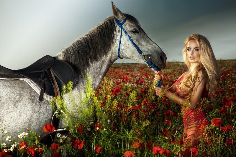 摆在与马的华美的白肤金发的妇女。 库存图片