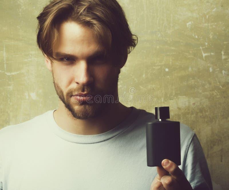 摆在与黑香水瓶的英俊的人 库存照片