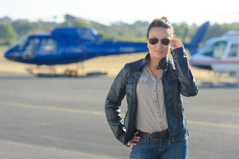 摆在与直升机的俏丽的试验妇女在背景中 免版税库存图片