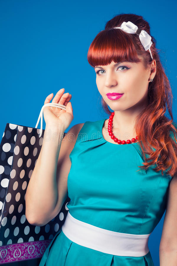 摆在与购物袋的美丽的画报女孩反对蓝色bac 库存照片