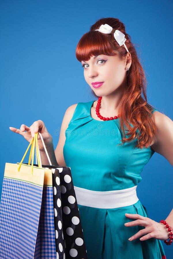 摆在与购物袋的美丽的画报女孩反对蓝色bac 免版税库存图片