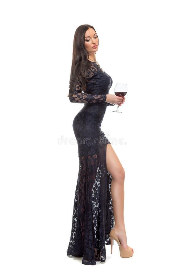摆在与玻璃酒isol的晚礼服的引诱的性感的妇女 图库摄影