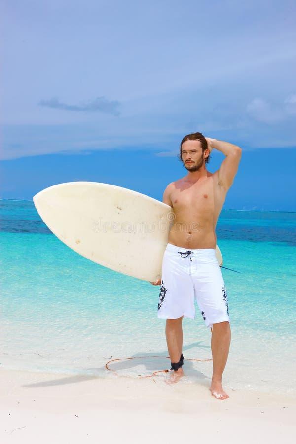 摆在与他的冲浪板的英俊的冲浪者 库存图片