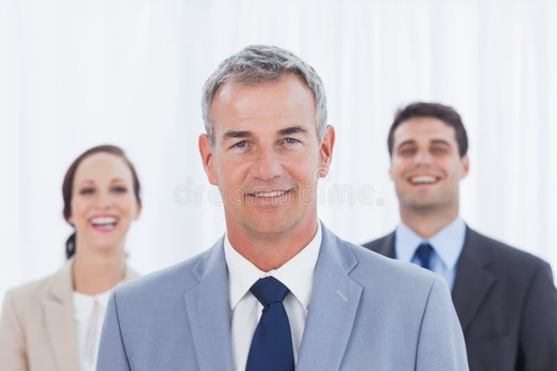 摆在与他的工作队的老练的商人 库存照片