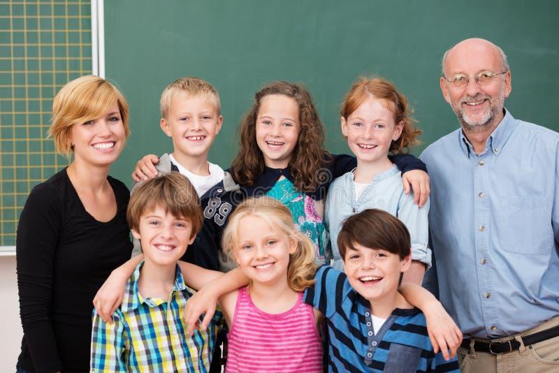 摆在与他们的老师的年轻学生类  免版税库存图片