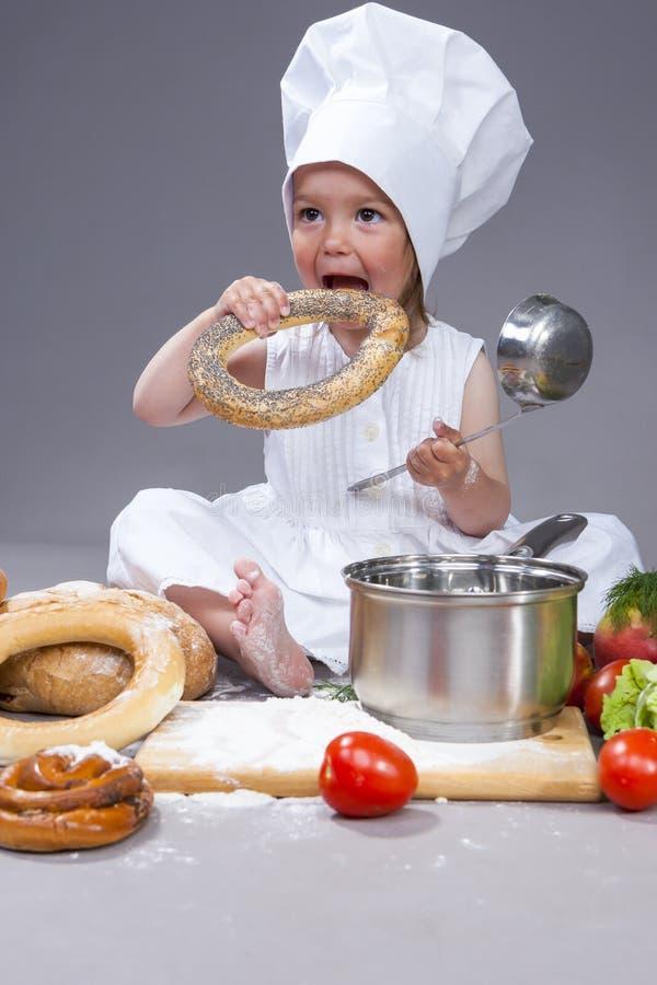 摆在与Doughnat小圆面包、瓢和平底深锅的厨师制服的白种人女孩在演播室 免版税库存图片