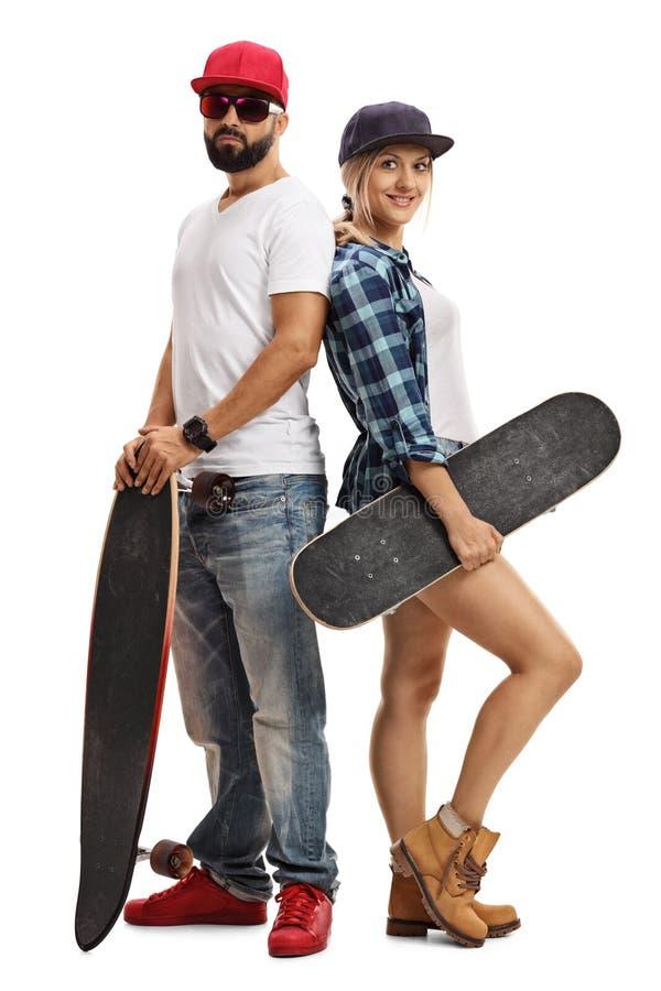 摆在与longboard和滑板的MMale和女性溜冰者 免版税库存照片