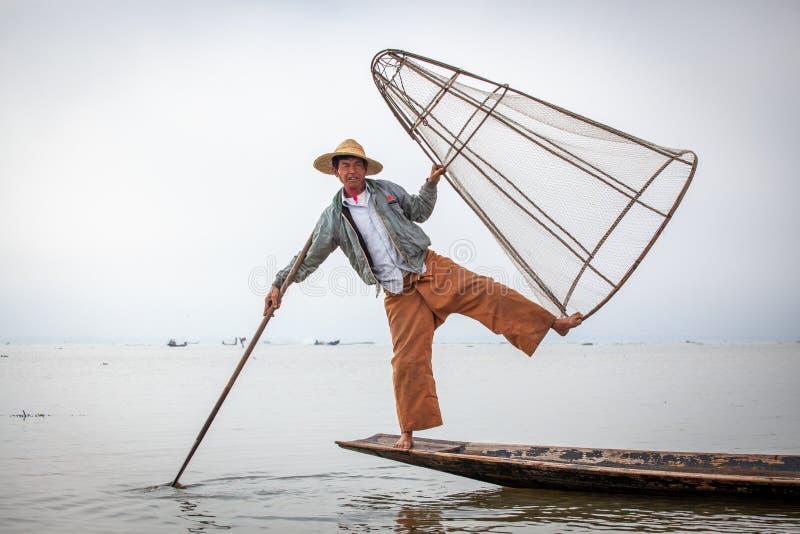 摆在为一传统渔船的游人的缅甸渔夫在Inle湖,缅甸 免版税图库摄影