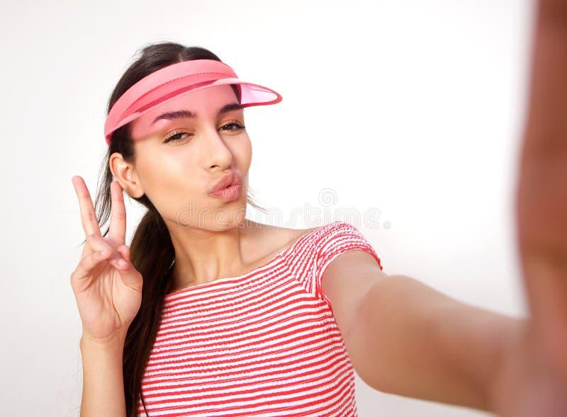 摆在为与和平手标志的selfie的美丽的女孩 库存照片
