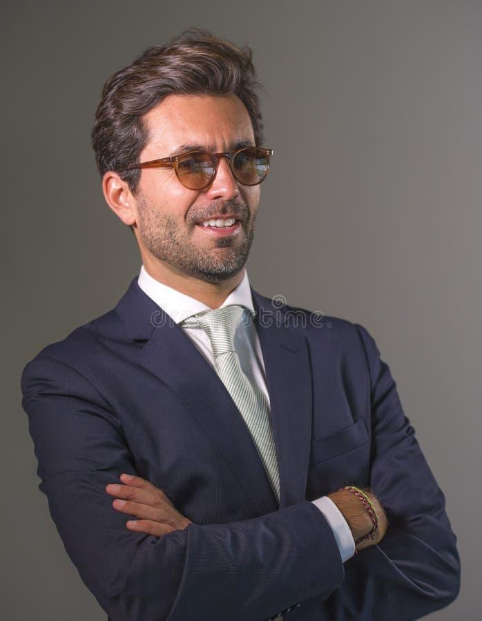 摆在为公司公司业务画象的衣服的典雅和英俊的愉快的人放松了和确信微笑的愉快被隔绝 免版税图库摄影