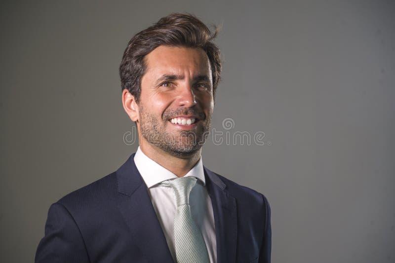 摆在为公司公司业务画象的衣服的英俊的愉快的人放松了和确信微笑的愉快隔绝在灰色  库存照片