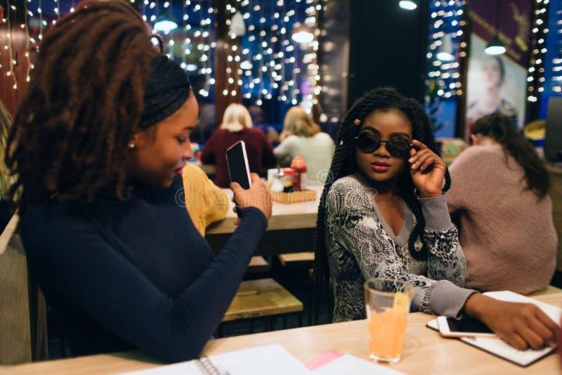 摆在为图片的非洲模型的图片 她握在太阳镜的手 她的朋友拍在电话的照片 他们坐 免版税库存照片