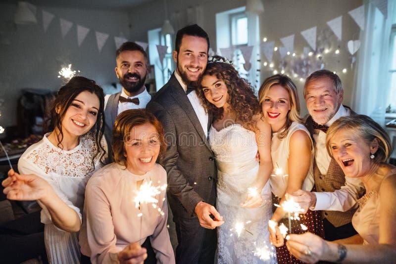 摆在为在一个结婚宴会的一张照片的一个年轻新娘、新郎和客人 库存图片