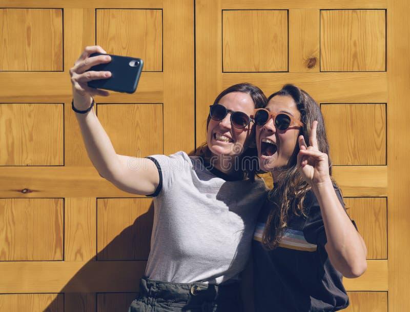 摆在为在一个黄色门的一selfie的一对微笑的女同性恋的年轻夫妇的画象 幸福和快乐的生活方式概念 免版税图库摄影