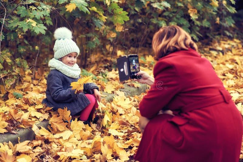 摆在为她的母亲的女孩在秋天公园 拍与您的智能手机的照片 免版税图库摄影
