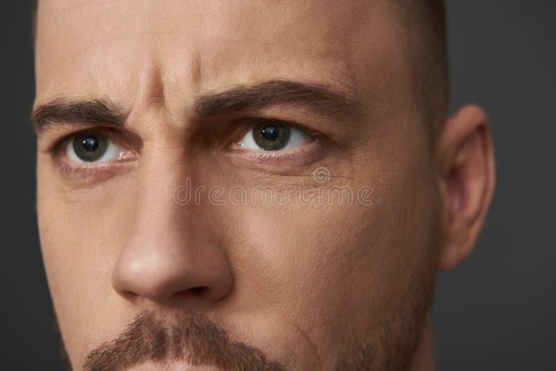 摆在为照相机的严肃的有胡子的年轻人接近的画象  库存图片