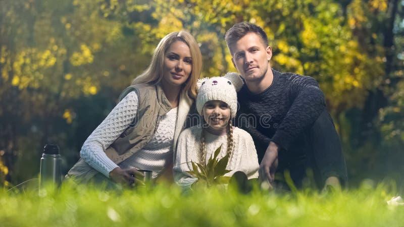 摆在为照相机的妈咪爸爸和女儿在秋天森林里,射击为photobook 免版税图库摄影