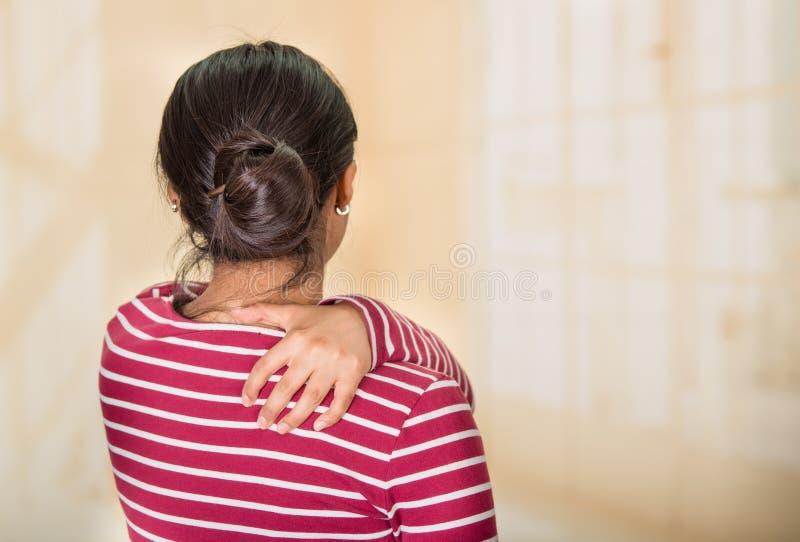 摆在为照相机的年轻西班牙妇女显示肩膀痛苦的迹象,握在痛苦的身体局部的手,伤害 免版税库存图片