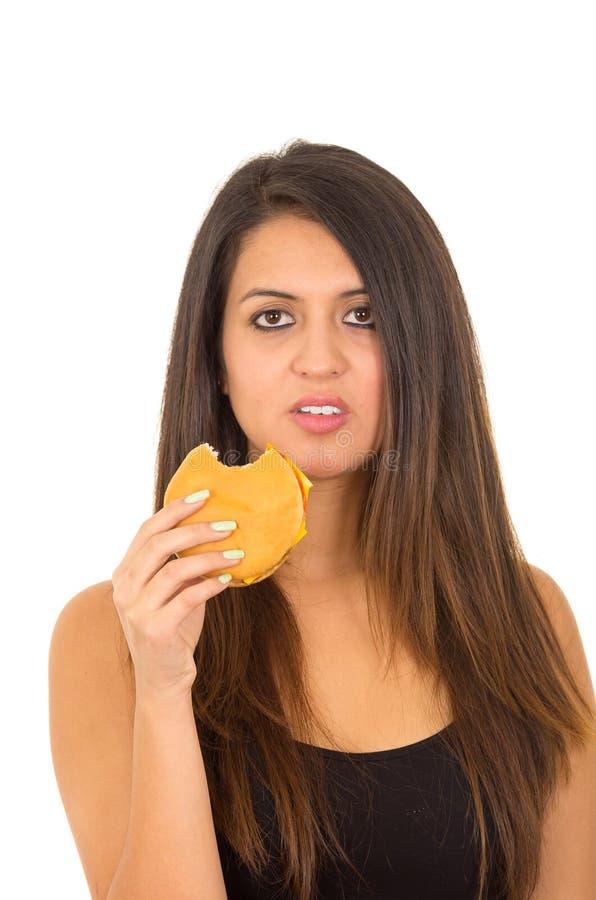 摆在为照相机的画象美丽的少妇吃汉堡包,当做有罪表情,白色演播室时 免版税库存照片