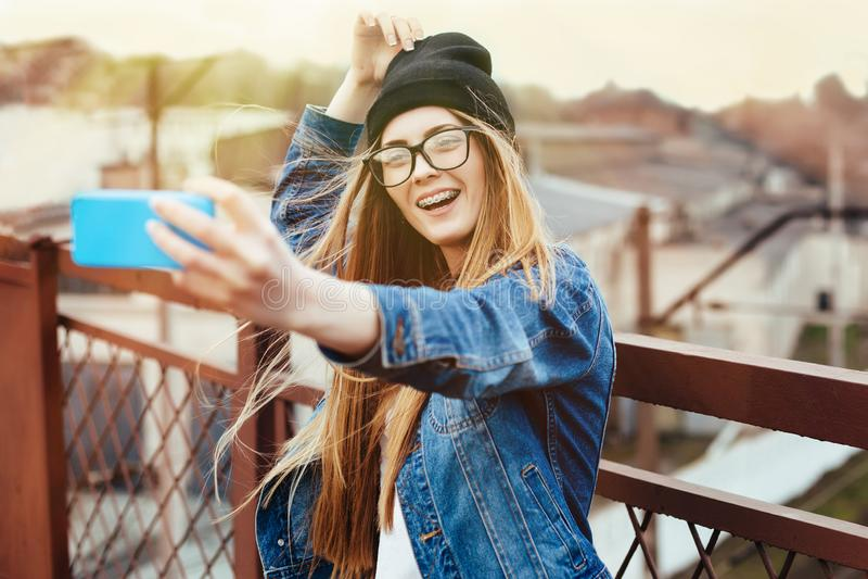 摆在为selfie和笑的年轻性感的白肤金发的行家妇女 佩带的牛仔裤夹克,行家黑帽会议和玻璃 E 库存图片