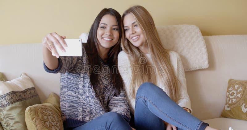 摆在为selfie的两个俏丽的女孩 库存照片