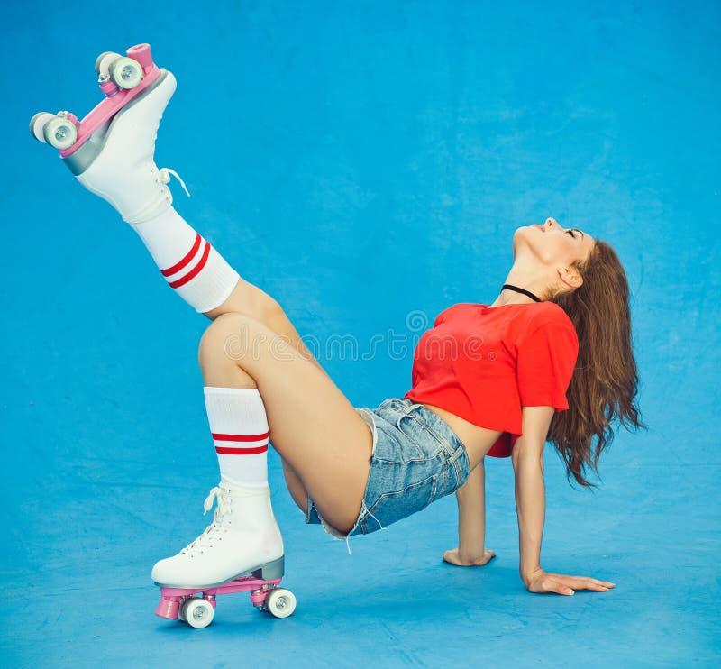 摆在举的腿在牛仔布短裤和一个红顶的美丽的深色头发的妇女在葡萄酒路辗德比夏日  库存照片