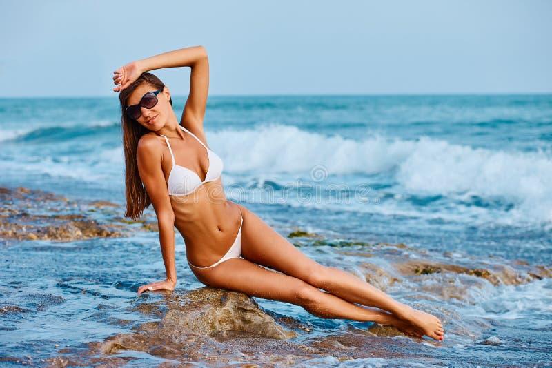 摆在五颜六色的游泳衣比基尼泳装的性感的美丽的被晒黑的妇女画象在沿海异乎寻常的国家旅行和休息 免版税库存图片
