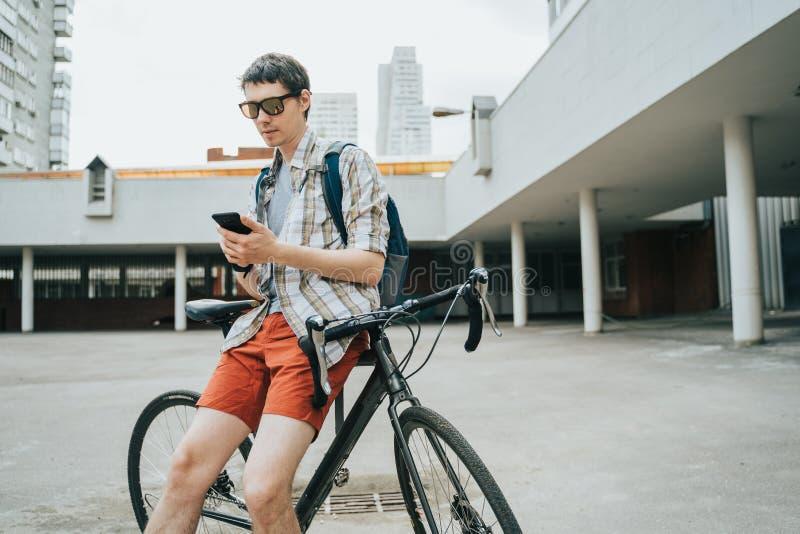 摆在他的自行车旁边的人 免版税库存图片