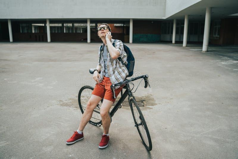 摆在他的自行车旁边的人 库存图片