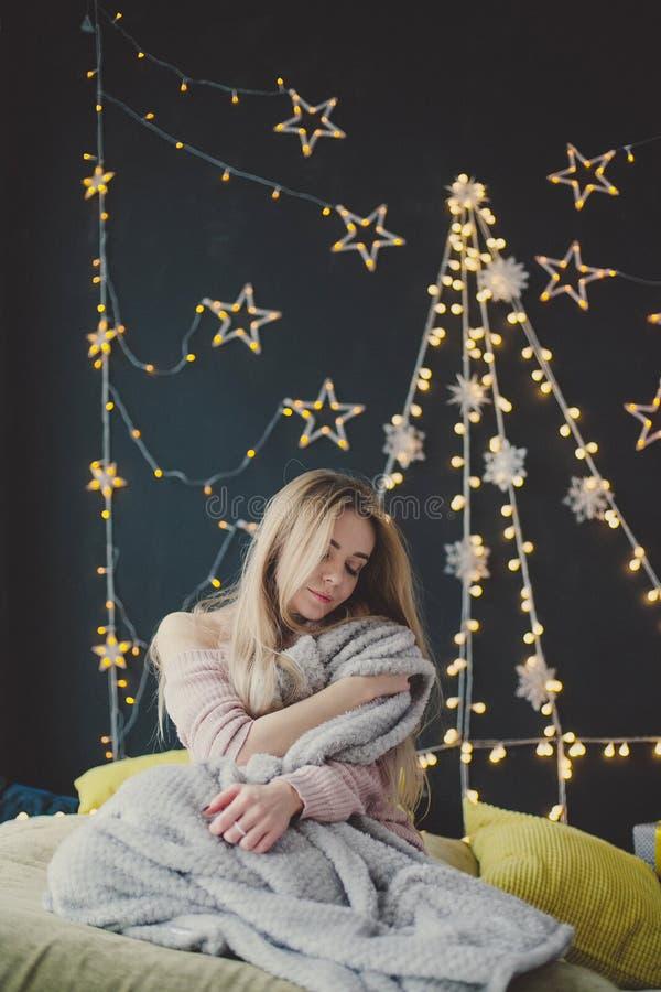摆在以圣诞节诗歌选为背景的格子花呢披肩的年轻女人 免版税图库摄影