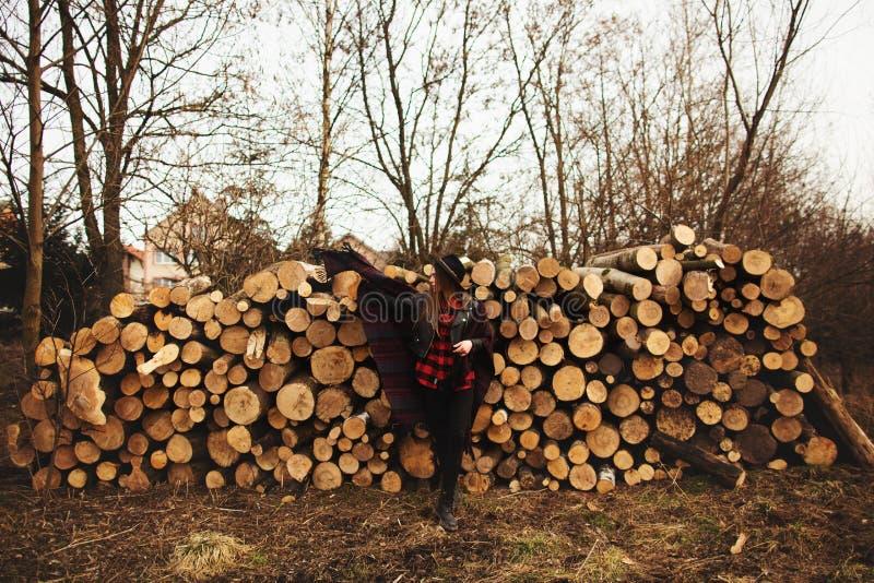 摆在以木柴为背景的黑帽会议的女孩 免版税图库摄影