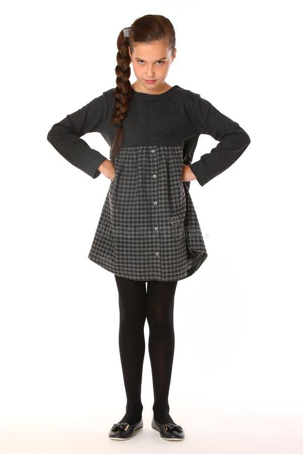 摆在企业衣裳的美丽的女小学生 她是严肃和过分要求的 库存图片