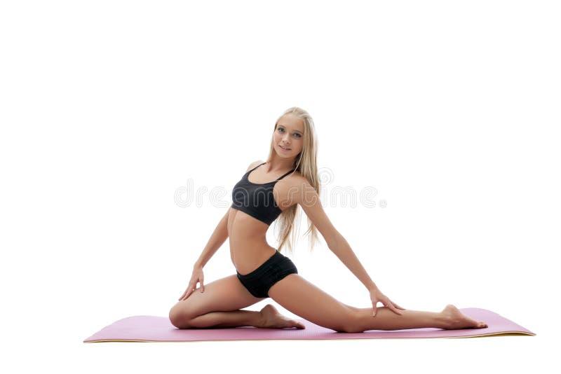 摆在体操席子的俏丽的健身辅导员 库存照片