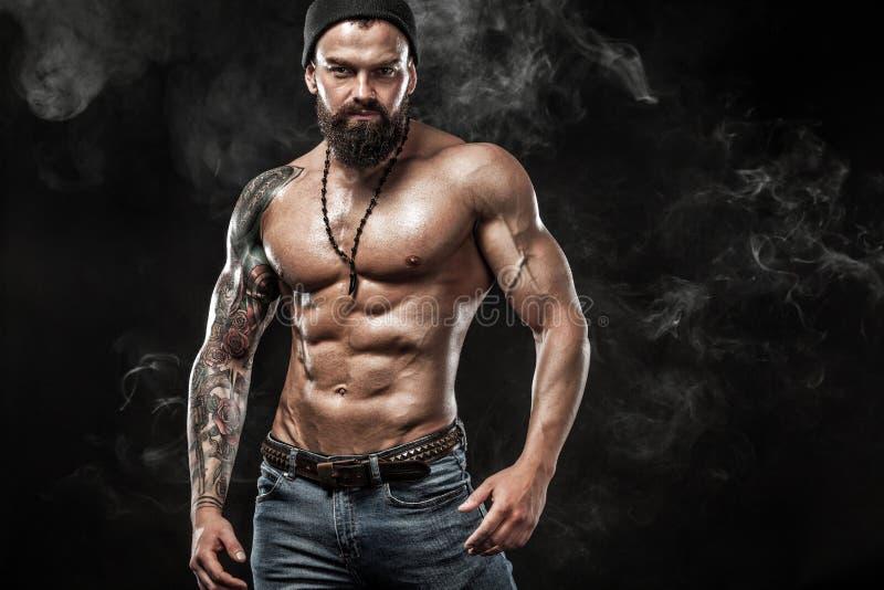 摆在佩带在有纹身花刺的牛仔裤的英俊的适合人 在黑背景隔绝的体育和时尚概念 库存照片