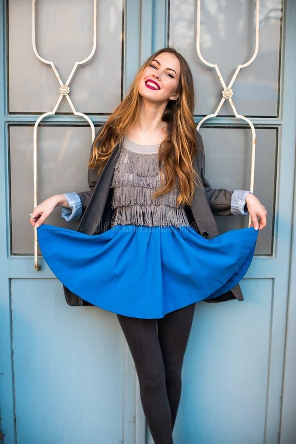 摆在佩带的便衣和蓝色裙子的美丽的微笑的少妇 库存照片
