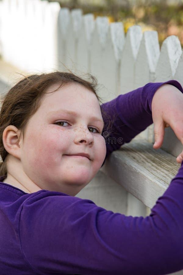 摆在倾斜在尖桩篱栅的女孩 免版税库存图片
