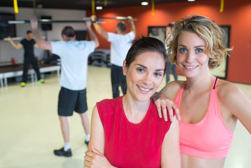 摆在健身房和微笑的愉快的妇女 免版税库存图片