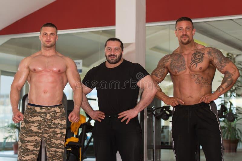 摆在健身房的小组爱好健美者 库存照片