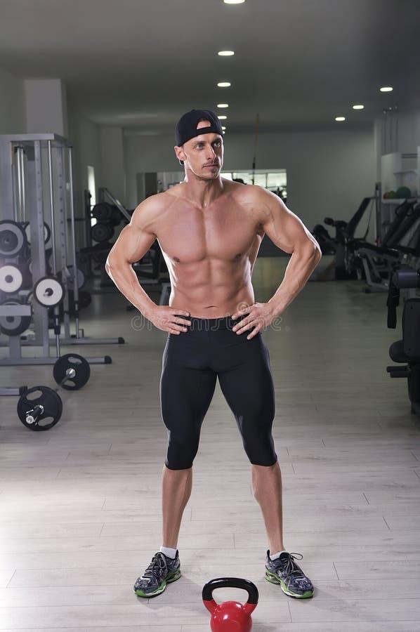 摆在健身房的英俊的强有力的运动人 免版税图库摄影
