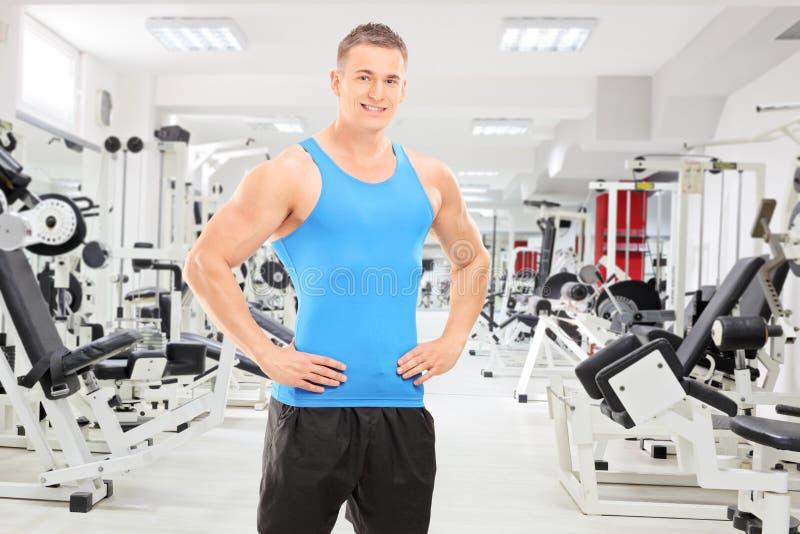 摆在健身房的年轻男性运动员 免版税库存照片